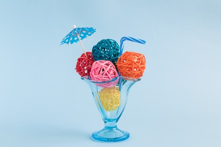 Sundae ice cream with colorful ice cream balls made of rattan balls, paper umbrella and drinking straw in cup against pastel blue background minimal concept.