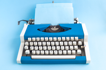 Typewriter with blank paper on pastel blue background minimal creative concept. Space for copy.