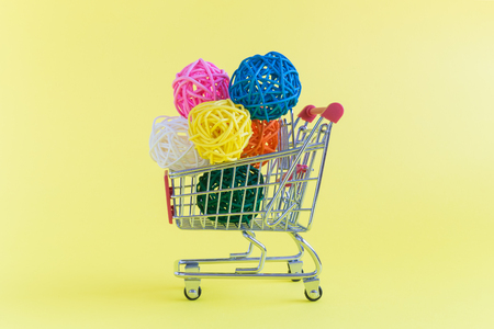 Shopping trolley toy full of colorful rattan balls on pastel yellow background minimal concept