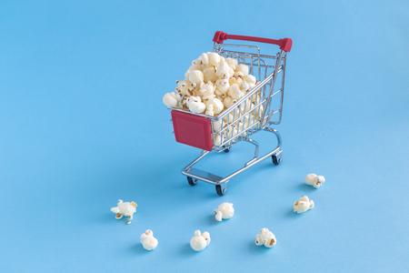 Shopping trolley toy full of popcorn on pastel blue background minimal concept. Reklamní fotografie