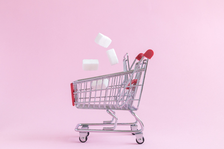 Sugar cubes falling into small shopping cart toy model on pastel pink background minimal creative concept.