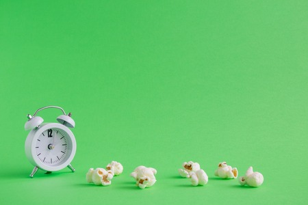 Popcorn and small alarm clock on pastel green background minimal creative concept. Space for copy.