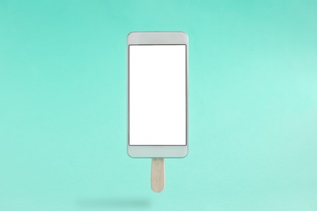 Mobile phone in form of ice cream isolated on pastel green background minimal concept. Reklamní fotografie