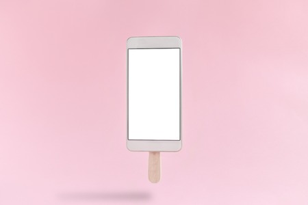 Mobile phone in form of ice cream isolated on pastel rose background minimal concept.
