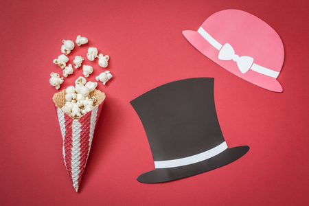 Flat lay of cone and popcorn with man and woman paper prop hats on red background minimal movie theater concept Reklamní fotografie