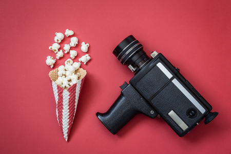 Flat lay of cone with popcorn and retro camcorder on red background minimal movie theater concept 版權商用圖片