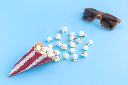 Popcorn with ice cream cone and 3d glasses on pastel blue background minimal cinema creative concept