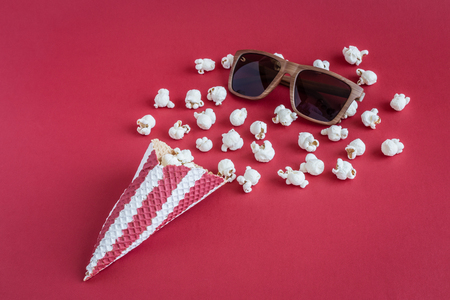 Popcorn with ice cream cone and 3d glasses on red background minimal cinema creative concept
