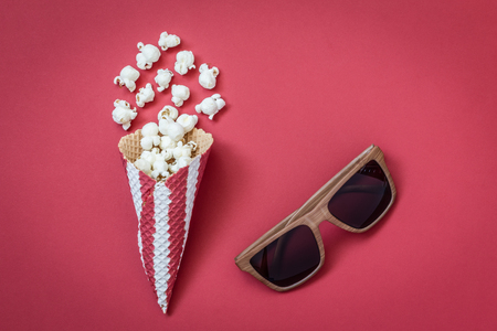 Flat lay of popcorn with ice cream cone and 3d glasses on red background minimal cinema creative concept