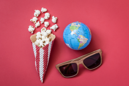 Flat lay of popcorn with ice cream cone, 3d glasses and globe on red background minimal cinema creative concept 版權商用圖片