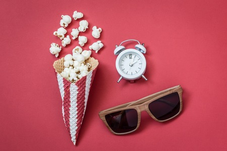 Flat lay of popcorn with ice cream cone, 3d glasses and alarm clock on red background minimal cinema creative concept