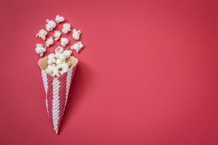 Flat lay of ice cream cone with popcorn isolated on red background minimal creative concept.