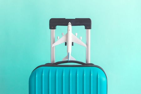 Suitcase and airplane model on pastel green background minimal creative travel concept Reklamní fotografie