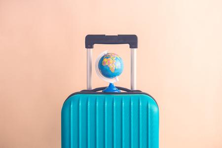 Suitcase and world globe model on pastel beige background minimal creative travel concept