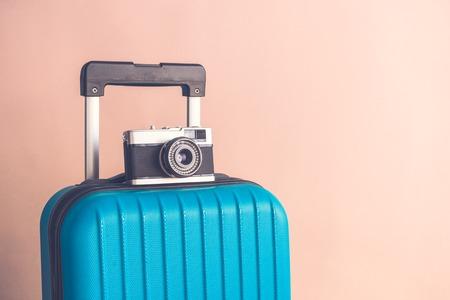 Suitcase and retro film camera on pastel beige background minimal creative travel concept