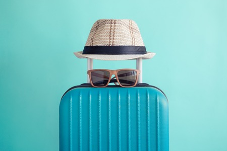 Suitcase with hat and sunglasses on pastel green background minimal creative travel concept Reklamní fotografie