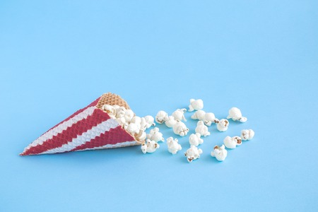 Ice cream cone with popcorn isolated on pastel blue background minimal creative concept. Reklamní fotografie