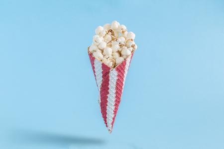 Ice cream cone with popcorn isolated on pastel blue background minimal creative concept. 版權商用圖片