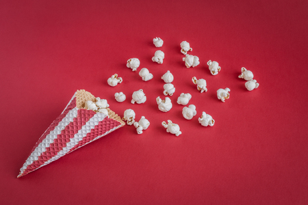 Ice cream cone with popcorn isolated on red background minimal creative concept. Reklamní fotografie
