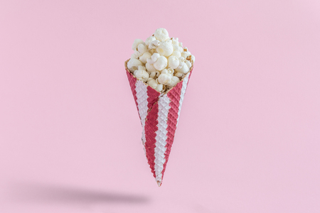 Ice cream cone with popcorn isolated on pastel pink background minimal creative concept.
