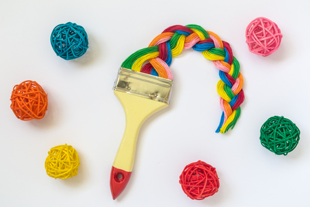 Paintbrush with long colorful strings braid and rattan balls isolated on white background minimal creative concept. Stock Photo