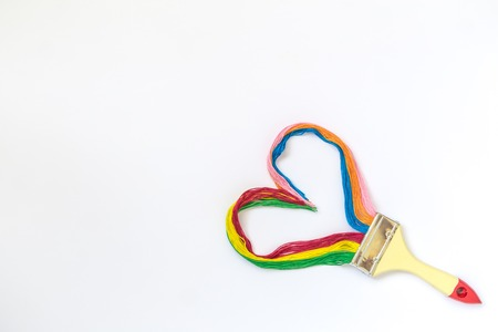 Paintbrush with long colorful strings in heart shape isolated on white background minimal creative concept. Space for copy.