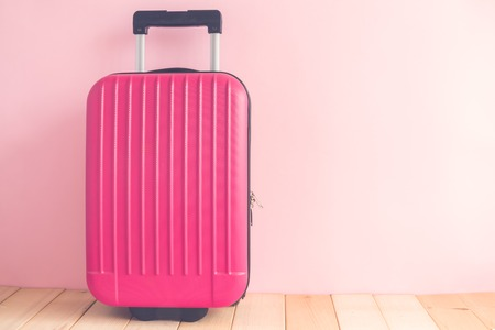 Pink suitcase against pastel rose wall minimal travel vacation creative concept. Space for copy. 版權商用圖片