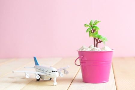 Airplane model toy and bucket full of sand with palm tree on table against pastel pink background minimal travel concept. Space for copy.