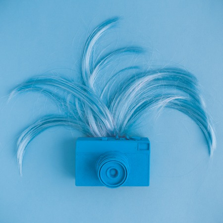 Retro camera and female hair flat lay in pastel blue color. Minimal fashion creative concept.