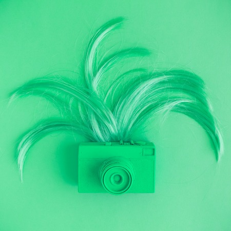 Retro camera and female hair flat lay in neon green color. Minimal fashion creative concept.