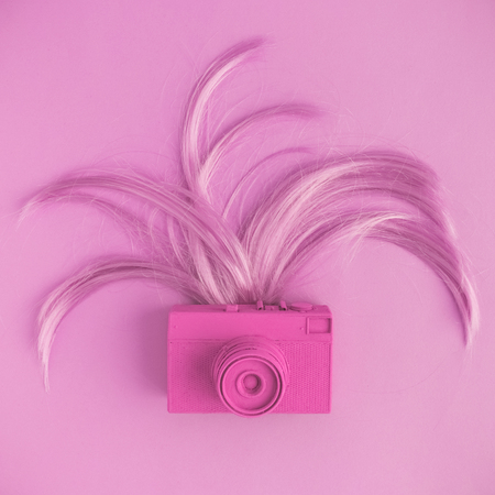 Retro camera and female hair flat lay in pastel pink color. Minimal fashion creative concept. Stok Fotoğraf