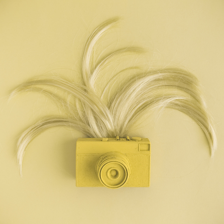 Retro camera and female hair flat lay in pastel yellow color. Minimal fashion creative concept.
