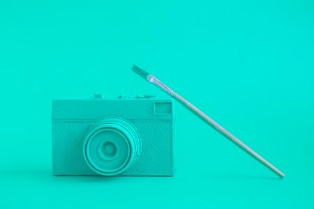 Turquoise retro film photo camera with paintbrush minimal art creative concept. Stockfoto