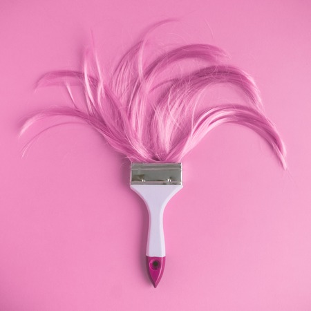 Paintbrush with long pink hair flat lay minimal creative background.
