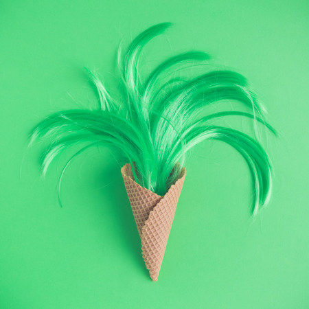 Ice cream cone and neon green hair flat lay minimal summer concept.