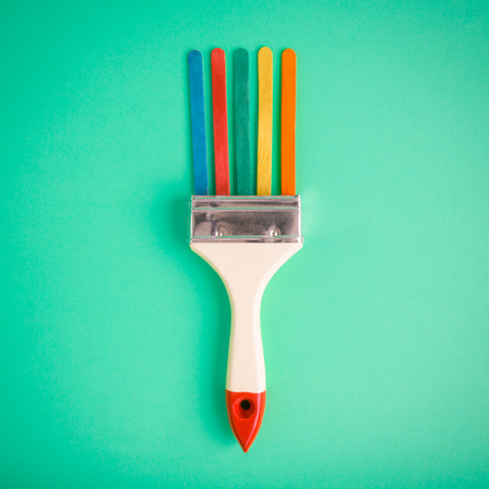 Paintbrush with colorful ice cream sticks on pastel green background minimal creative concept.