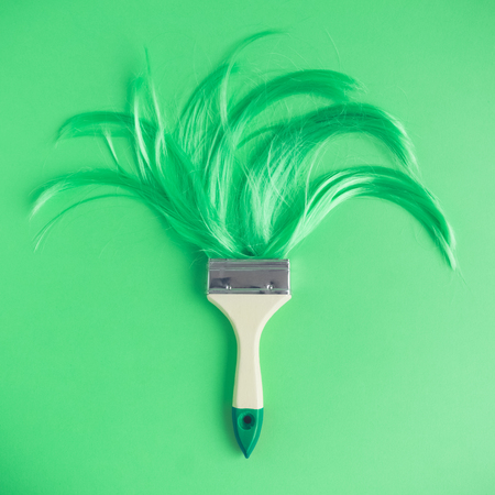 Paintbrush with long neon green hair flat lay minimal creative background.