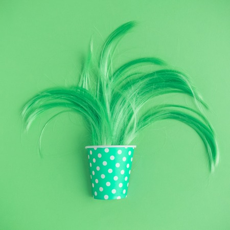 Flat lay of hair growing from polka paper cup in form of plant. Neon green colored creative minimal concept. Stock Photo