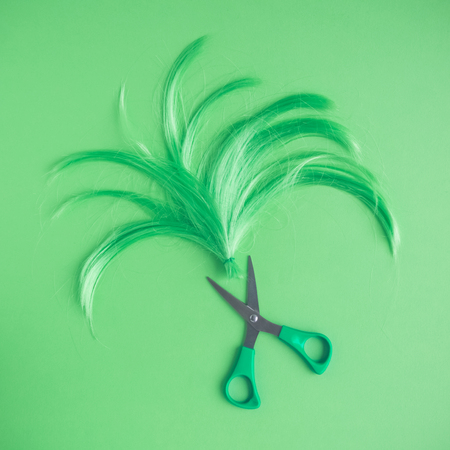 Wig and scissors neon green tone hairstyle background.