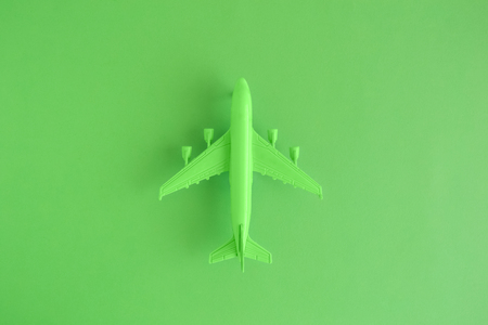 Flat lay of miniature toy airplane on neon green background minimal trip and travel creative concepts. Stock Photo