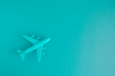 Flat lay of miniature toy airplane on blue background minimal trip and travel creative concepts. Space for copy.