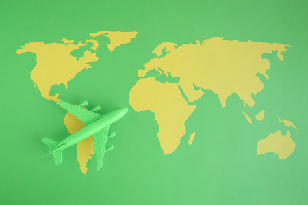 Flat lay of miniature toy airplane on green background with world map minimal trip and travel creative concepts.