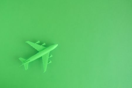 Flat lay of miniature toy airplane on neon green background minimal trip and travel creative concepts. Space for copy. Stock Photo