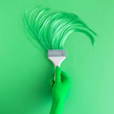 Hand holding paintbrush with long hair minimal abstract neon green creative concept.