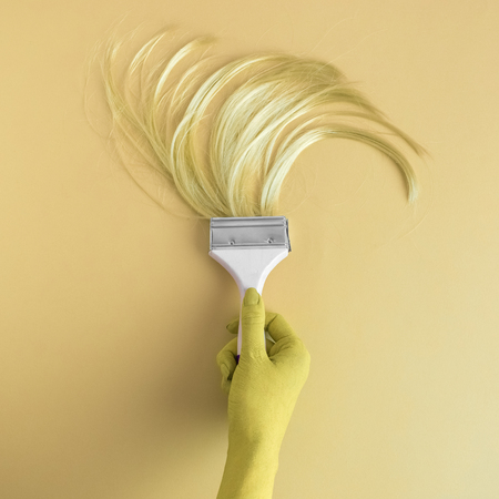 Hand holding paintbrush with long hair minimal abstract yellow creative concept.