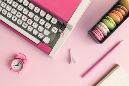Flat lay of typewriter, macaroons, alarm clock, Eiffel Tower miniature and notebook with pencil pink minimal creative concept. Stock Photo