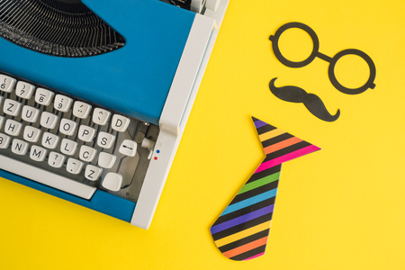 Flat lay of vintage blue typewriter and paper props in form of retro hipster man on yellow background minimal creative concept. Imagens