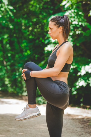 Athlete woman preparing for running in nature. Legs warming and stretching. Reklamní fotografie