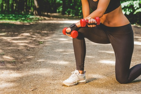 Close up of sportswoman holding weights in nature. Sport and healthy lifestyle concept.