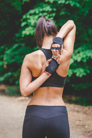 Female jogger stretching arms and back in nature.